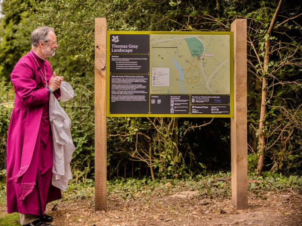 The Bishop of Buckingham studies the new information-board about Thomas Gray in Stoke Poges